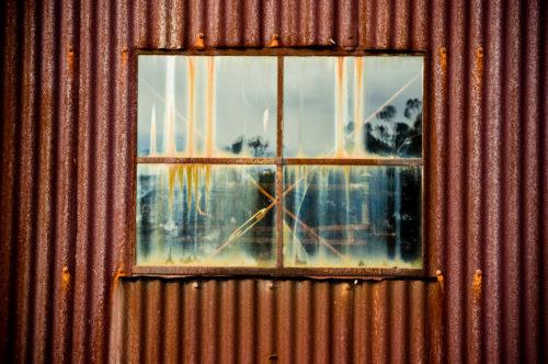 old rusty tin (corrugated iron) metal shed with window
