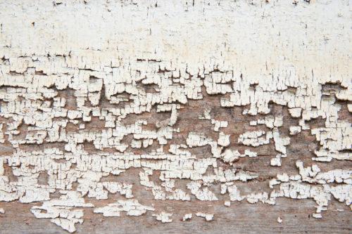closeup of peeling paint on the weatherboard wood texture