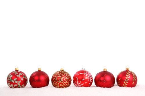 row of christmas balls on white