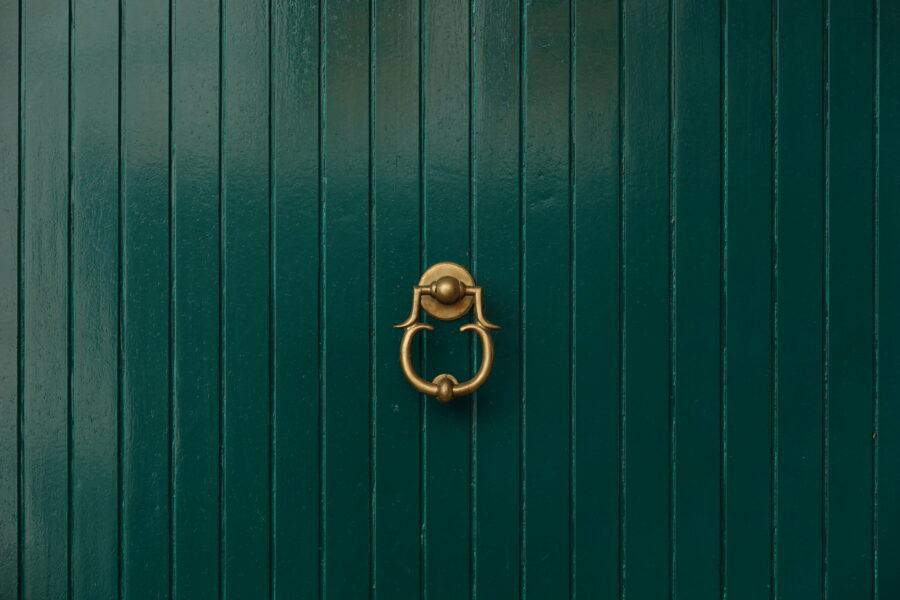 Green door with golden door knocker free stock photo. Landscape orientation.