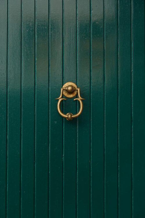 Green door with golden door knocker free stock photo. Portrait orientation.